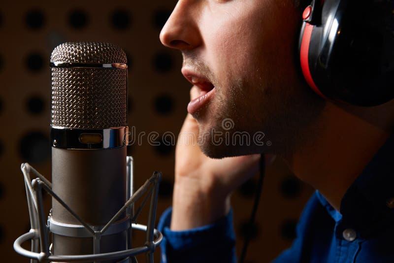 唱歌入话筒的男性歌唱者在录音室 免版税库存照片