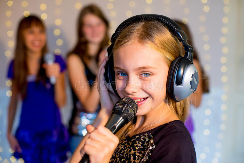 唱歌在卡拉OK演唱的小组愉快的女孩 免版税图库摄影