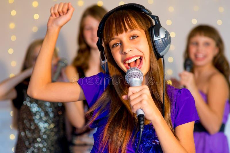 唱歌在卡拉OK演唱的小组愉快的女孩 免版税库存图片