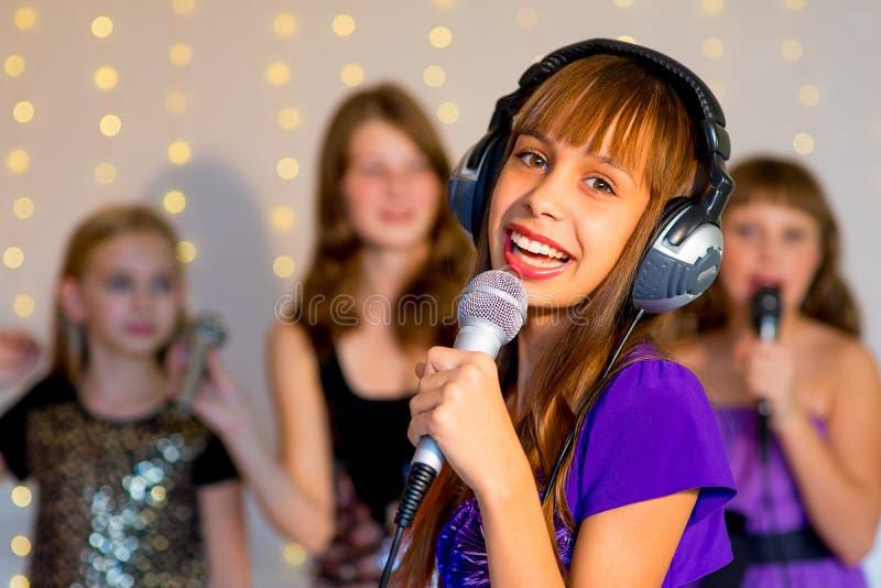 唱歌在卡拉OK演唱的小组愉快的女孩 免版税库存照片
