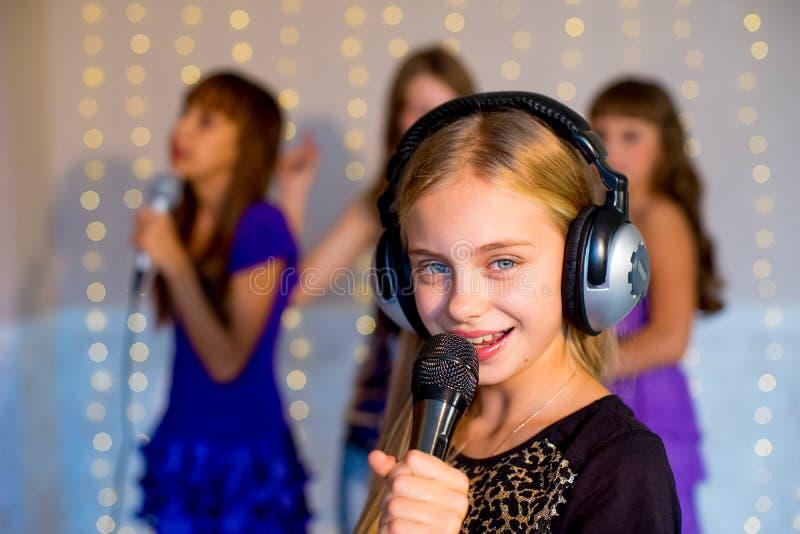 唱歌在卡拉OK演唱的小组愉快的女孩 图库摄影