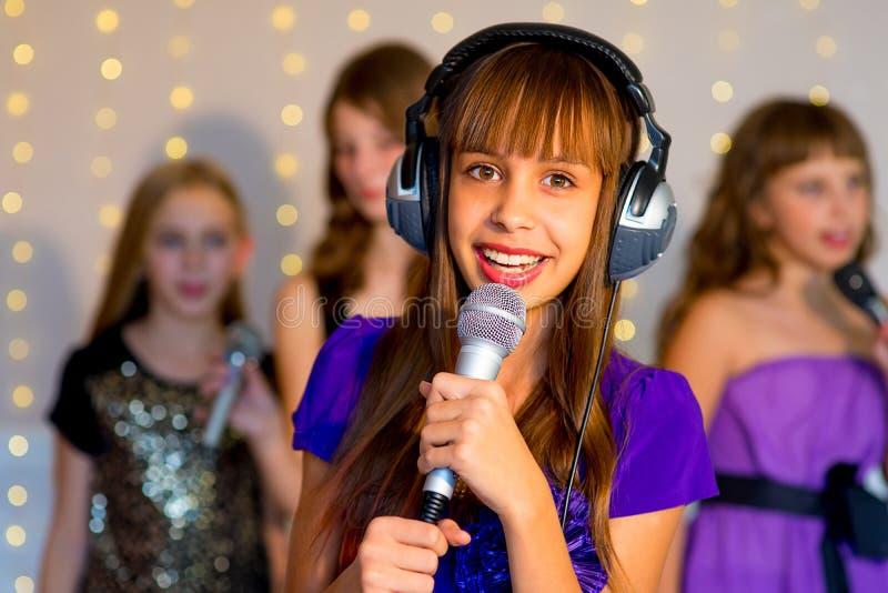 唱歌在卡拉OK演唱的小组愉快的女孩 库存图片