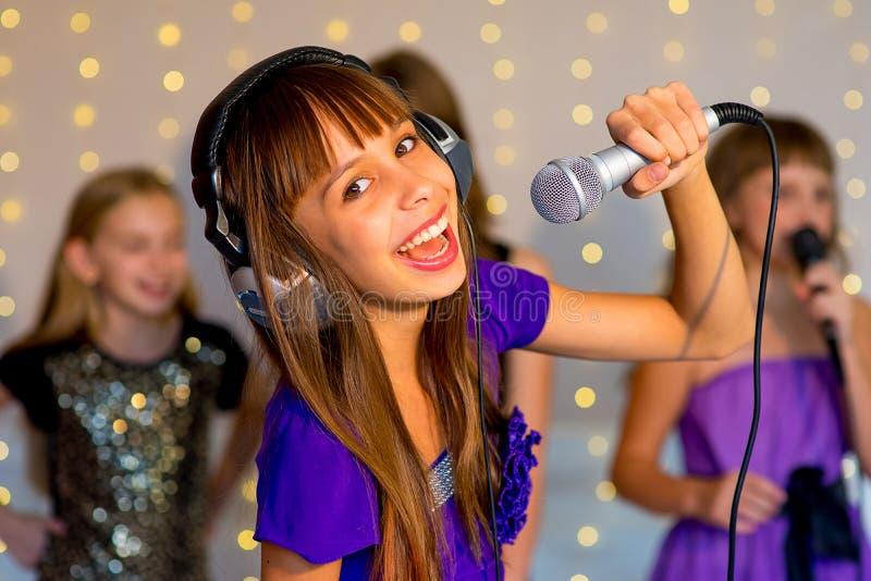 唱歌在卡拉OK演唱的小组愉快的女孩 库存照片