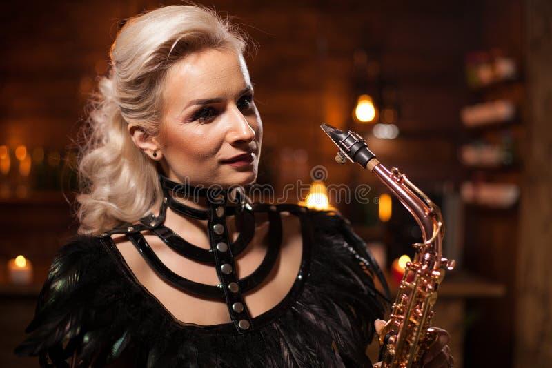 唱歌在她的萨克斯管的白种人妇女画象在葡萄酒客栈 免版税库存图片