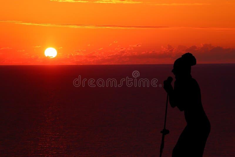 唱歌在日落剪影的女孩 库存图片