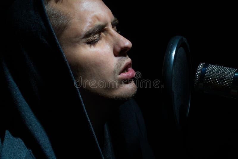 唱歌在有话筒的录音室的人 免版税库存照片