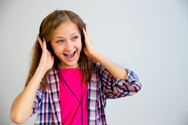 唱歌在耳机的女孩 库存照片