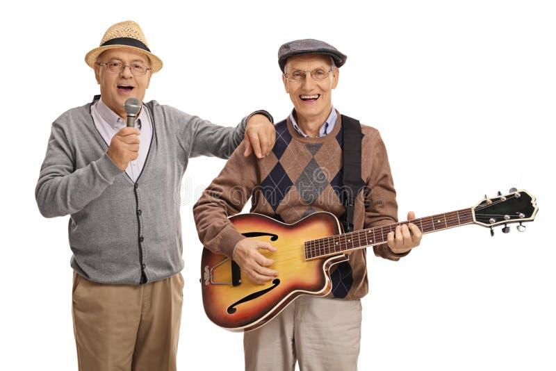 唱歌在话筒和另一年长人playin的年长人 免版税库存图片