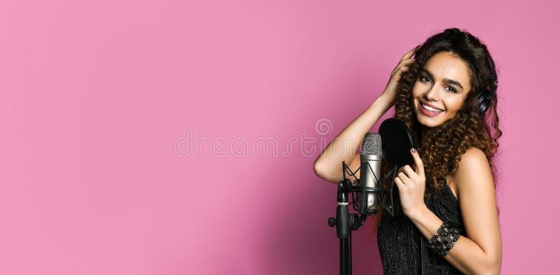唱歌在话筒被隔绝的关闭的年轻俏丽的妇女  免版税库存照片