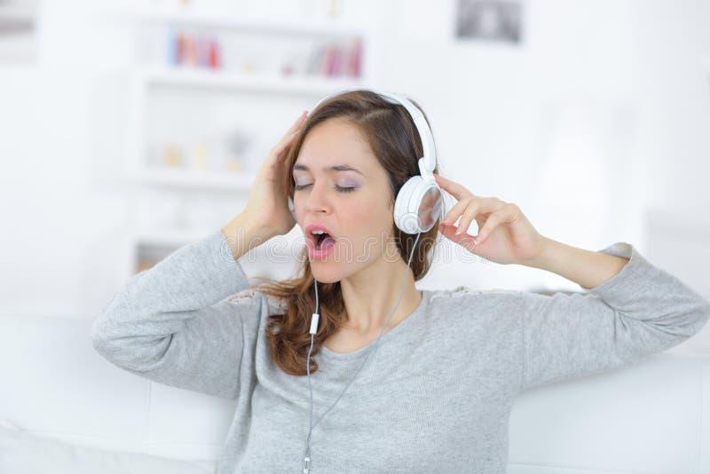 唱歌对在耳机的音乐的少妇 库存照片