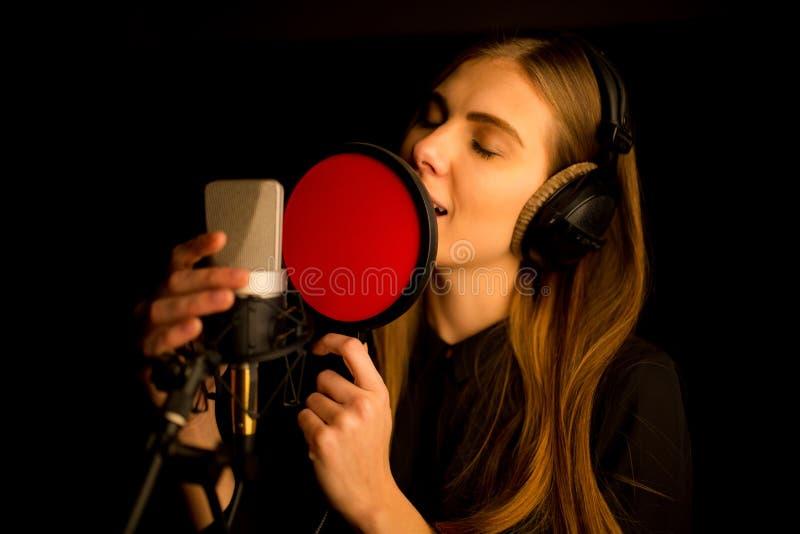 唱歌对话筒的女孩在演播室 创造新的歌曲的过程 免版税库存照片