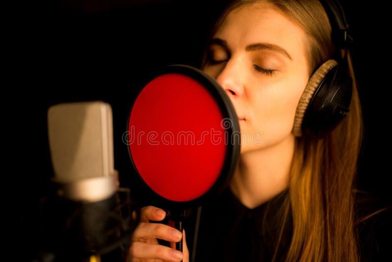 唱歌对话筒的女孩在演播室 创造新的歌曲的过程 免版税图库摄影