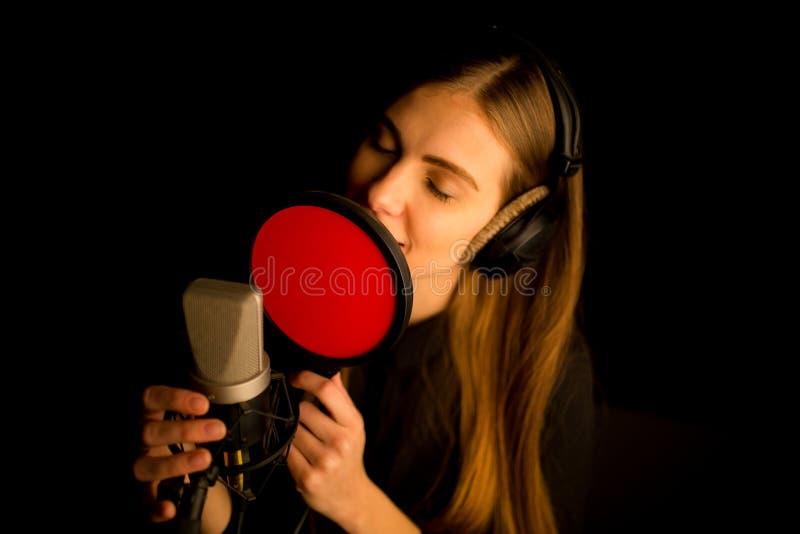 唱歌对话筒的女孩在演播室 创造新的歌曲的过程 库存照片
