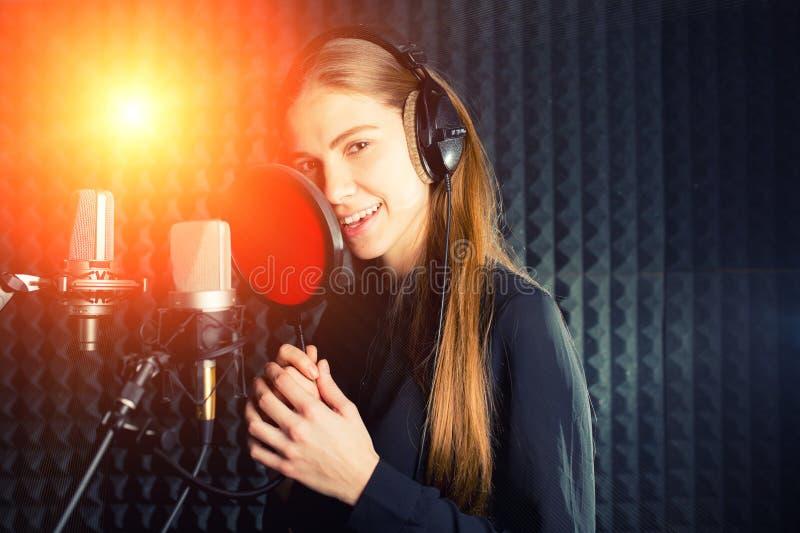 唱歌的女孩唱歌到专业话筒在记录演播室 过程由年轻歌手创造一支新的流行歌曲 免版税库存图片