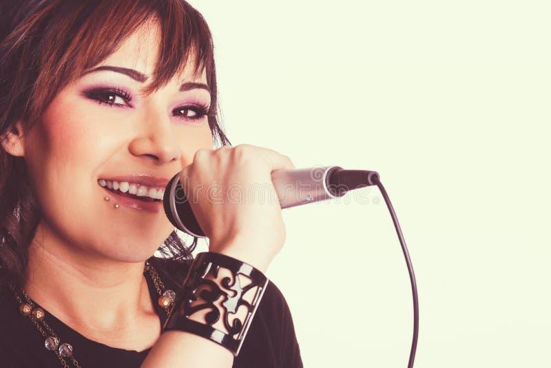 唱歌的年轻美丽的妇女 免版税库存图片