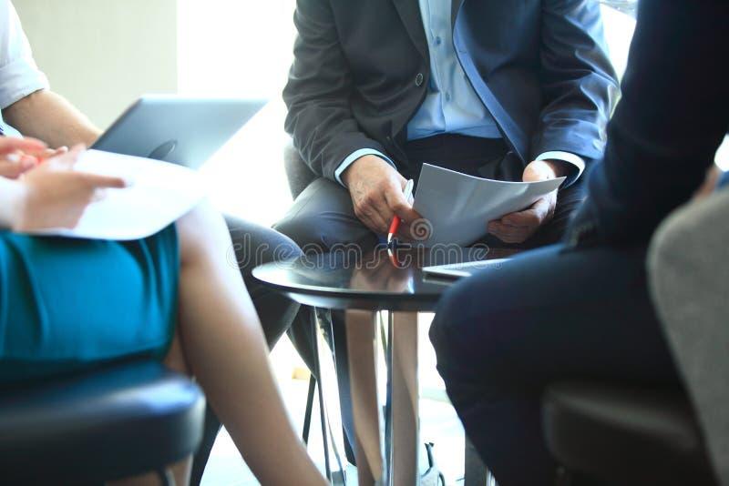 商业主持会议服务台查出在白色 一起坐会议和做笔记的青年人特写镜头  免版税库存图片