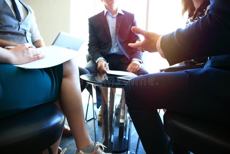 商业主持会议服务台查出在白色 一起坐会议和做笔记的青年人特写镜头  免版税库存照片