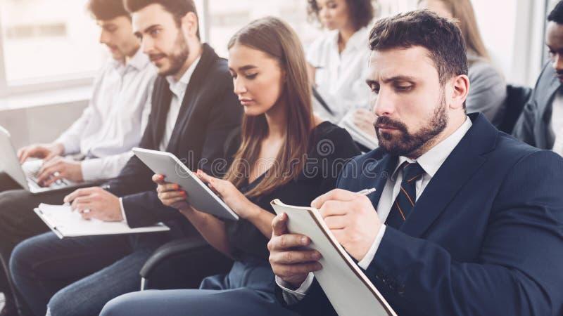 商业主持会议服务台查出在白色 做笔记的年轻人在办公室 免版税库存图片