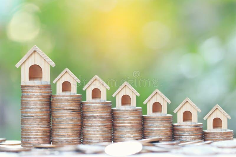 商业投资和不动产概念,堆的增长的式样房子在自然绿色背景的硬币金钱 免版税库存图片