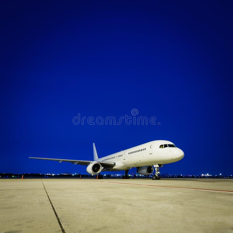 商业飞机在晚上 免版税库存图片