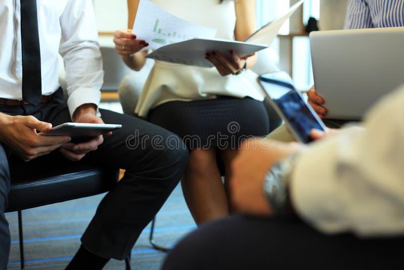 商业主持会议服务台查出在白色 一起坐会议和做笔记的青年人特写镜头  库存照片