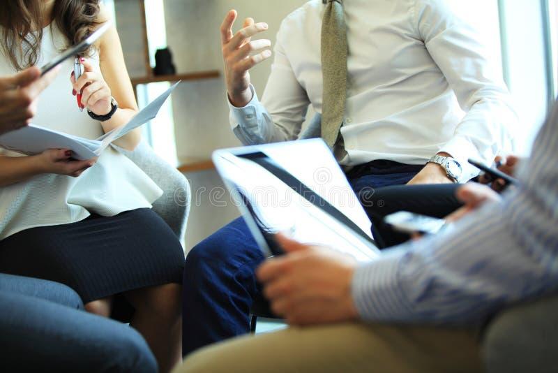 商业主持会议服务台查出在白色 一起坐会议和做笔记的青年人特写镜头  库存图片