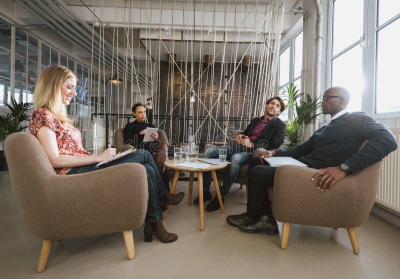 商人不同的队见面在办公室的游说 免版税库存照片