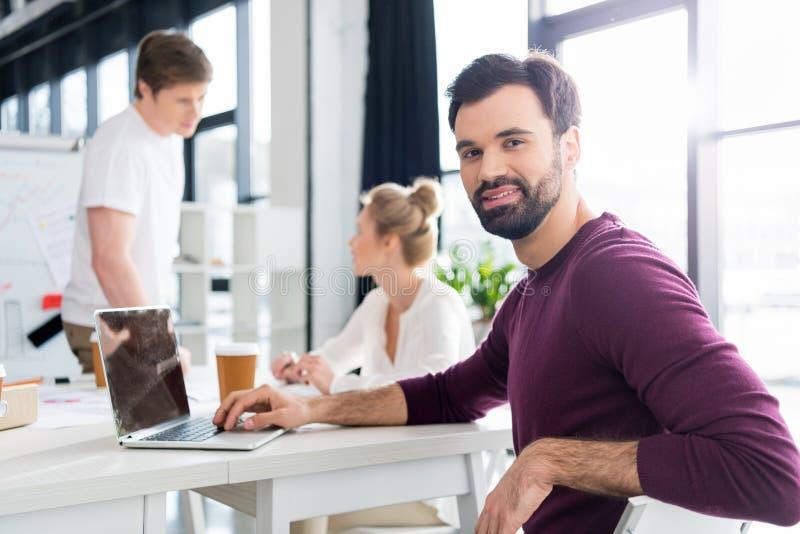 商人与在工作场所的后边膝上型计算机一起使用在办公室,同事 免版税库存照片