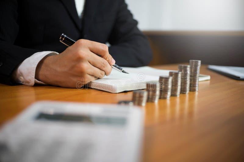 商人与在木桌上的收入报告文件一起使用 E 免版税库存图片
