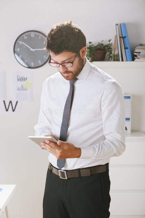 年轻商人与数字式片剂一起使用在办公室。 库存照片