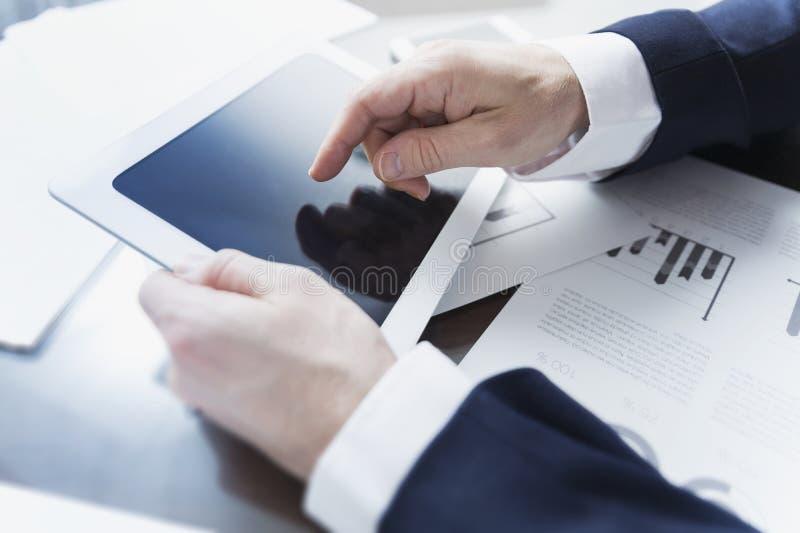 商人与数字式片剂一起使用在办公室 库存图片