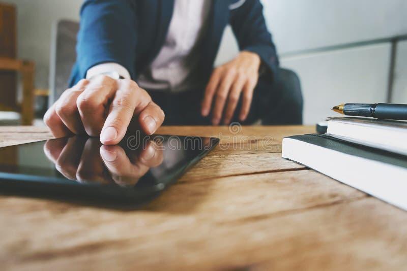 商人与数字片剂和膝上型计算机一起使用有财政经营战略的在工作场所 免版税库存图片