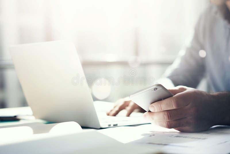 商人与普通设计笔记本一起使用 在手上拿着智能手机 水平,阳光作用 图库摄影