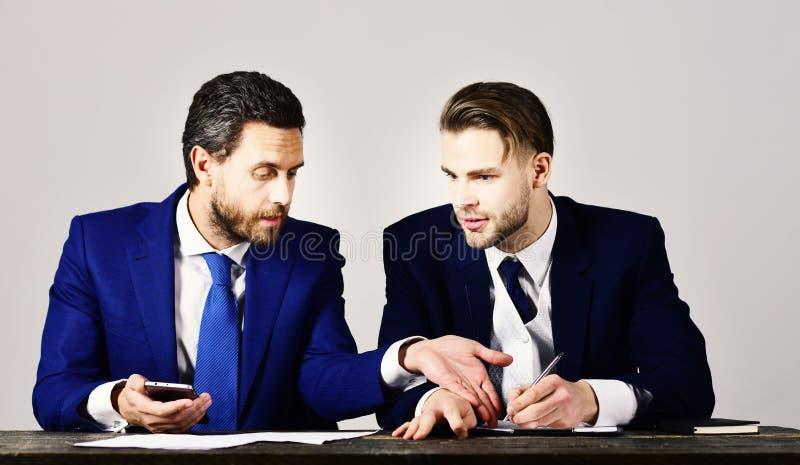 商人与有的财务专家协商严肃的面孔 免版税库存照片