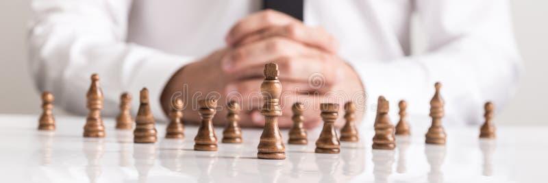 商人与棋的计划战略在白色桌上计算 免版税库存照片