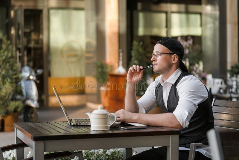 商人与膝上型计算机一起使用在室外咖啡馆 图库摄影