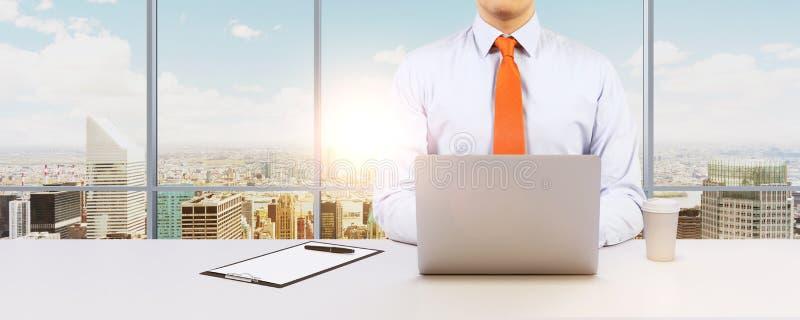 商人与膝上型计算机一起使用 现代全景办公室或工作地点有纽约视图 免版税库存图片