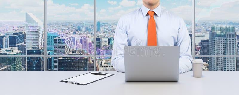 年轻商人与膝上型计算机一起使用 现代全景办公室或工作地点有纽约视图 免版税库存图片