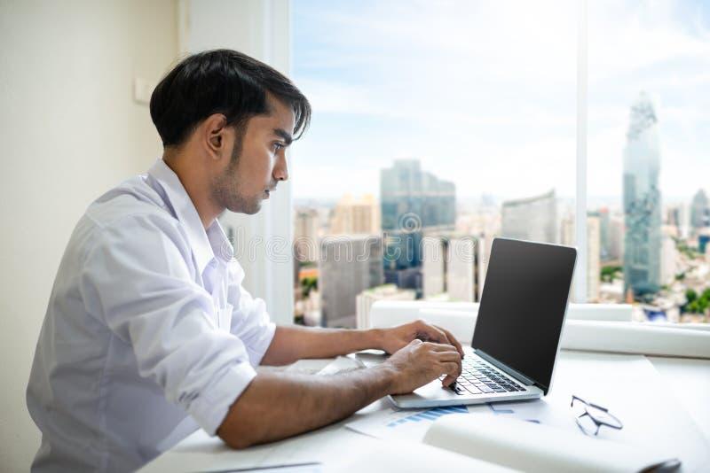 商人与膝上型计算机和文件一起使用 免版税图库摄影