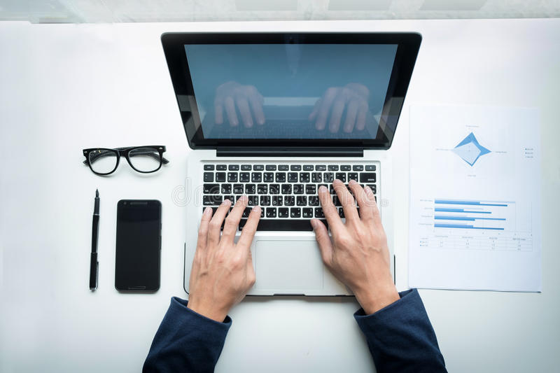 年轻商人与膝上型计算机和智能手机一起使用在他的des 免版税库存照片