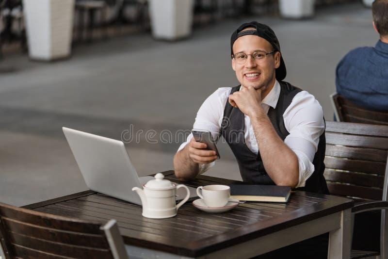 商人与膝上型计算机和电话一起使用在室外咖啡馆 库存图片