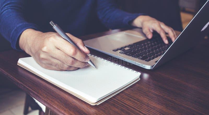 商人与膝上型计算机和笔记薄一起使用在书桌桌上 免版税库存照片