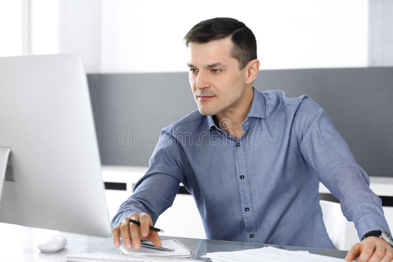 商人与计算机一起使用在现代办公室 男性企业家或公司董事特写工作场所的 免版税库存照片