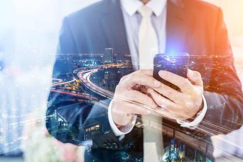 商人两次曝光使用智能手机的有citysca的 免版税库存图片