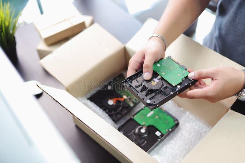 商人个人计算机和包裹的磁泡线厘或泡影的藏品硬盘的手板料在黑书桌上的小包箱子附近在家 库存照片