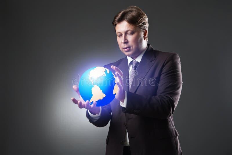 商人举行在黑暗的地球地球的手 免版税库存图片