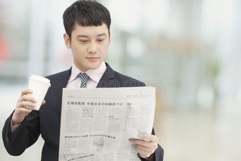 年轻商人举行的和饮用的咖啡早晨惯例和读报纸 库存图片