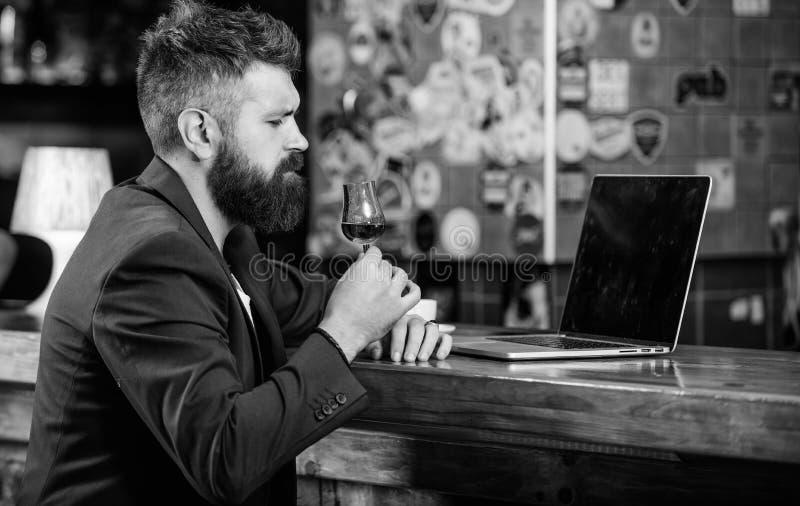 商人互联网冲浪饮料酒精 行家自由职业者工作网上饮用的科涅克白兰地 人有胡子的商人酒吧 免版税库存照片