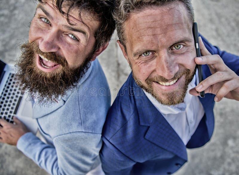 商人享受现代技术机会 商人举行膝上型计算机愉快的答复电话 ?? 免版税库存照片