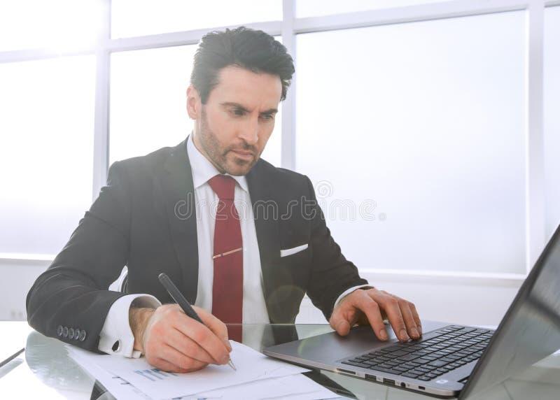 商人使用一台膝上型计算机检查财务数据 免版税库存图片